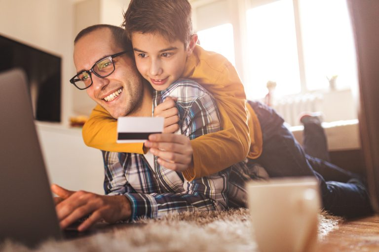Boy and dad with credit card and computer